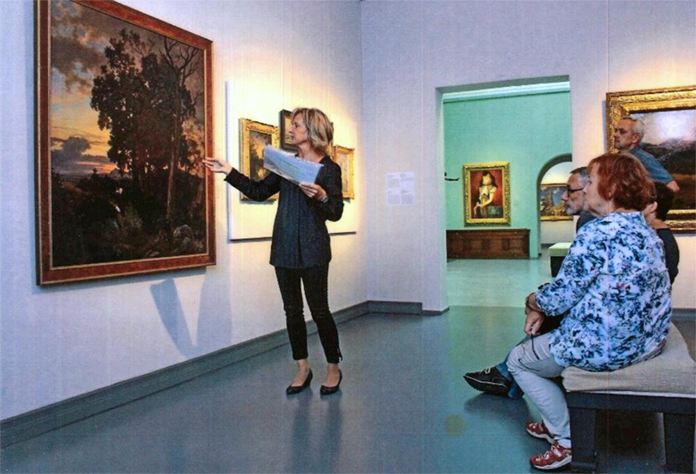 Frau im schwarzen Hosenanzug steht vor einem Ölgemälde und erläutert dies den Besuchern (zwei Männern und eine Frau).